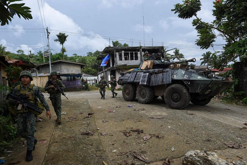 Philippine marines walk next to an armoured vehicle after engaging militants in Marawi, on June 2, 2017.