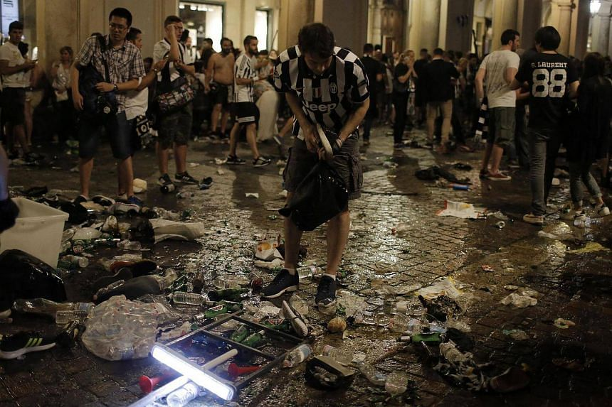 Juventus' supporters look for personal belongings in Piazza San Carlo after a panic movement in the fanzone where thousands of Juventus fans were watching the Uefa Champions League Final football match between Juventus and Real Madrid.