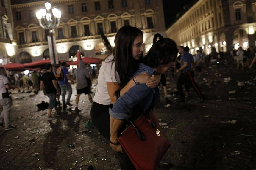 Juventus' supporters evacuate the Piazza San Carlo after a panic movement in the fanzone where thousands of Juventus fans watched the Uefa Champions League Final football match between Juventus and Real Madrid.