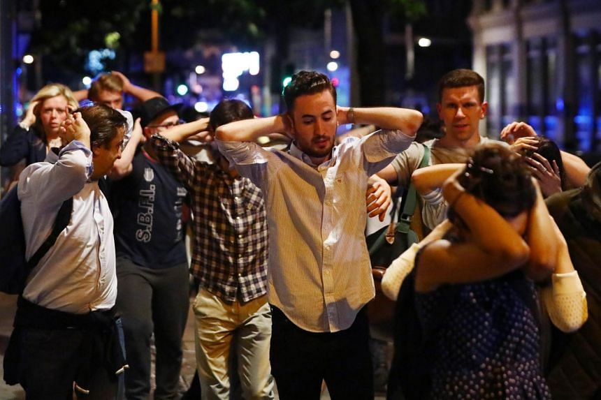 People leave the area with their hands up after an incident near London Bridge in London.