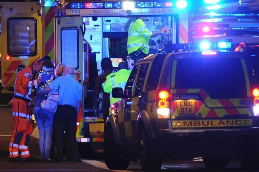 Members of the emergency services attend to persons injured in an apparent terror attack on London Bridge.