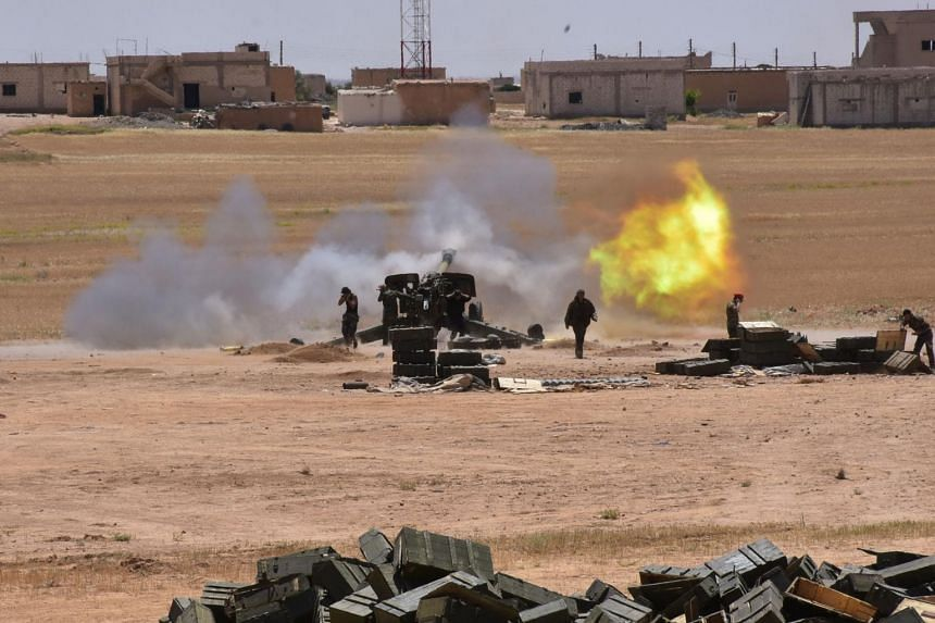 Syrian government forces firing artillery against the Islamic State group on May 16,  in the town of Maskaneh.