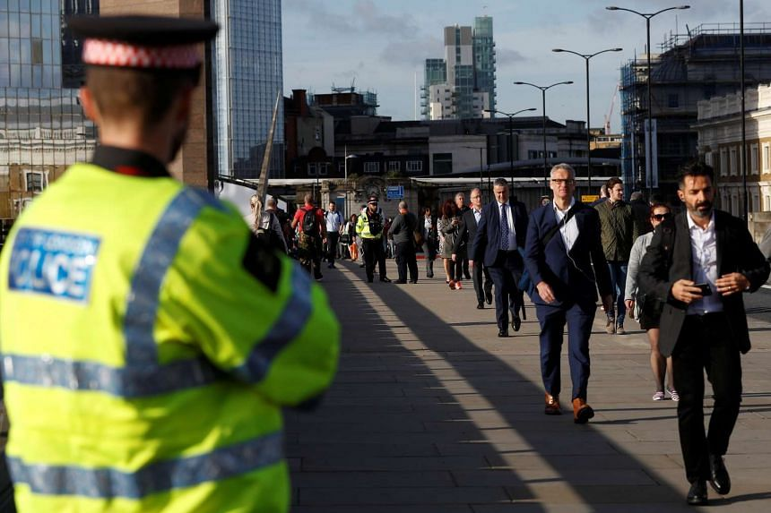 Commuters walk past a City of London police officer standing on London Bridge after is was reopened following an attack which left 7 people dead and dozens of injured in central London, Britain on June 5, 2017.