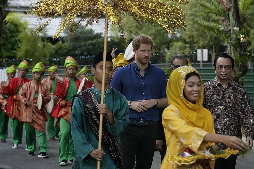 Prince Harry receiving a traditional welcome at Jamiyah Children's Home. Later, he was given a silat demonstration led by former world champion Sheik Alauddin Yacoob Marican and took part in an iftar, or the breaking of fast during Ramadan, with 80 y