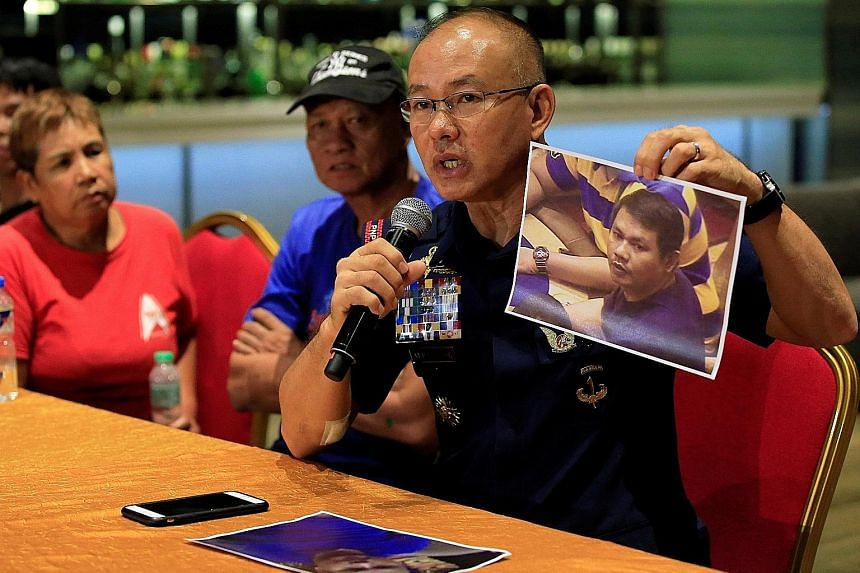 Chief Superintendent Oscar Albayalde with a photo of gunman Jessie Carlos at yesterday's press conference in Manila, with Carlos' mother Teodora and father Fernando. He said Carlos' casino attack was not an act of terrorism.