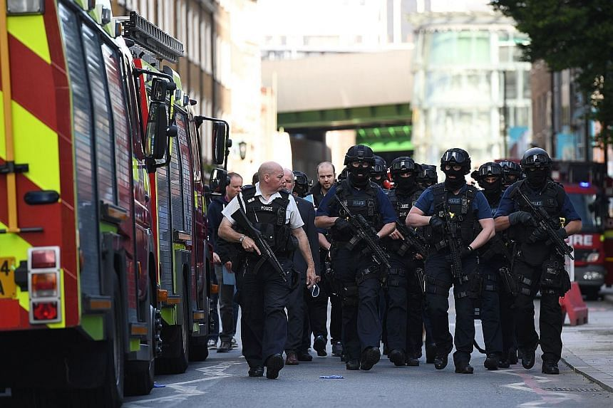 A woman being detained following a raid at a block of flats in Barking in east London yesterday. British police have arrested 12 people in connection with last Saturday's attack. Police officers near the London Bridge area, following last Saturday's