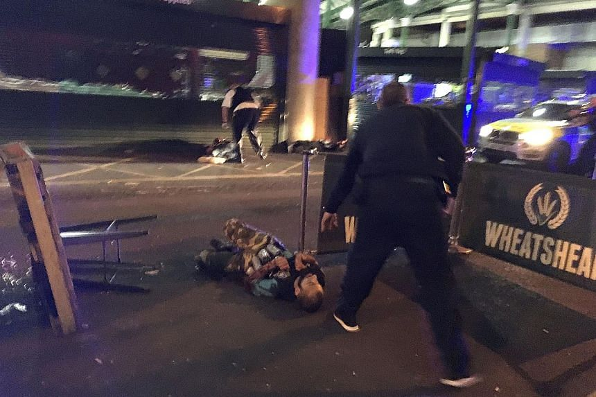 Police standing over two suspects shot at the scene of a terror attack outside Borough Market in central London last Saturday. The attack claimed seven lives and left more than 40 injured. Yesterday, police arrested as many as 12 people after raiding