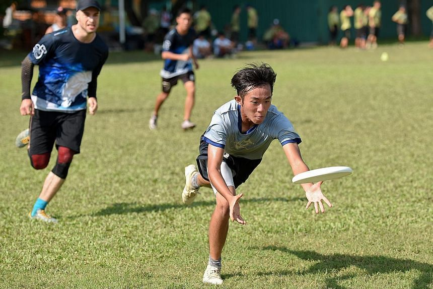 Chua Boon Hui, 18, of the Disctractors Club, receiving a pass against opponents Thirsty Camels at the UPA(S) Mixed Nationals yesterday.