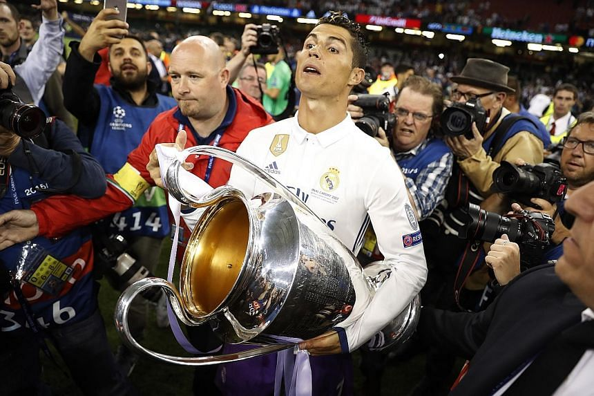 Real Madrid forward Cristiano Ronaldo celebrating with the Champions League trophy. The Spanish side became the first team to retain the Cup in its current format.