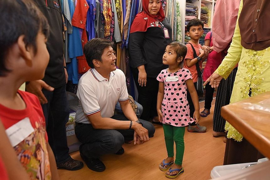 Mr Ng Chee Meng with four-year-old Aliya Natasha at a store in Tanjong Katong Complex. She was among 80 children from low-income families in Punggol North who were taken to the mall for a shopping trip. The children also received new baju kurungs.