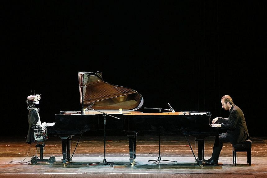 A 53-finger robot pianist called Teotronica and Italian pianist Roberto Prosseda performing on twin grand pianos at a theatre in Tianjin, north China, on Saturday. The rhythmic bot reportedly can distinguish between the speed of key change and play v