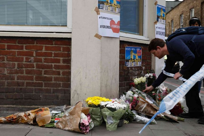 A man lays flowers at a police cordon on Borough High Street, in London, on June 4, 2017.