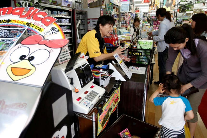 Shoppers line up in front of cashiers at the Don Quijote's central branch store in Tokyo on May 28, 2014.