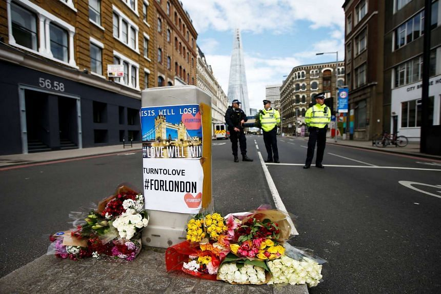Flowers and messages lie behind police cordon tape near Borough Market on June 4, 2017.
