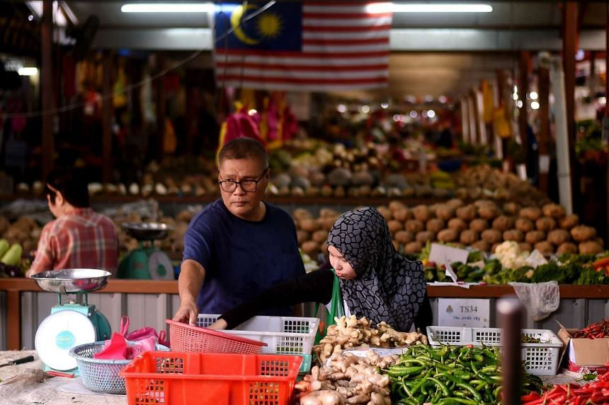 A family shopping for vegetables at a wholesale market in Kuala Lumpur, on May 19, 2017.