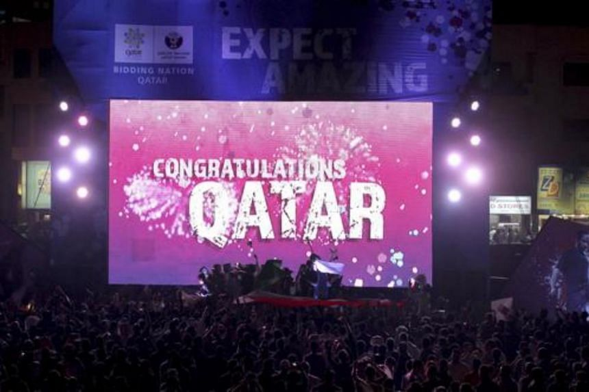 """People celebrate in front of a screen that reads """"Congratulations Qatar"""" after FIFA announced that Qatar will be host of the 2022 World Cup in Souq Waqif in Doha on Dec 2, 2010."""