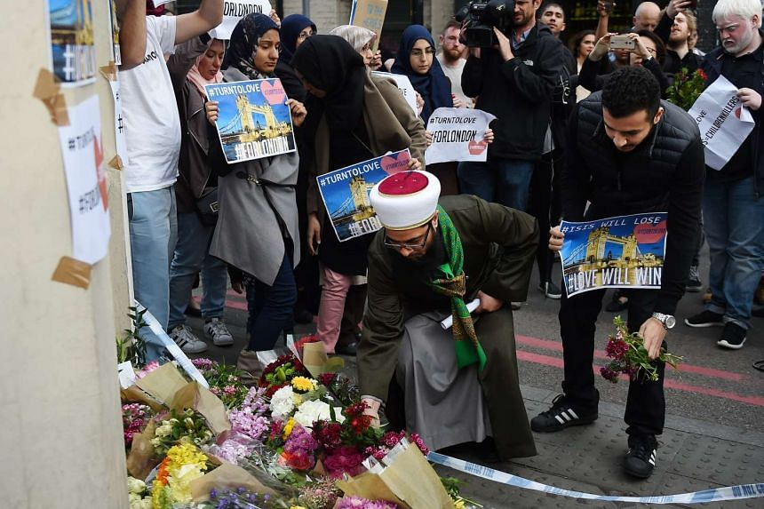 Members of London's Muslim community hold signs of condolence and support near the site of an attack at Borough Market in London on June 4, 2017.