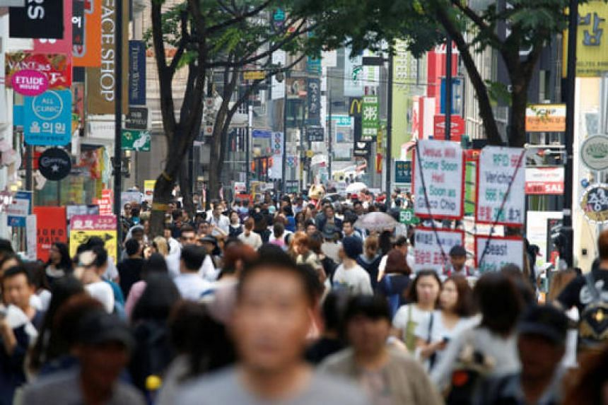 People walk in Myeongdong shopping district in Seoul, South Korea.