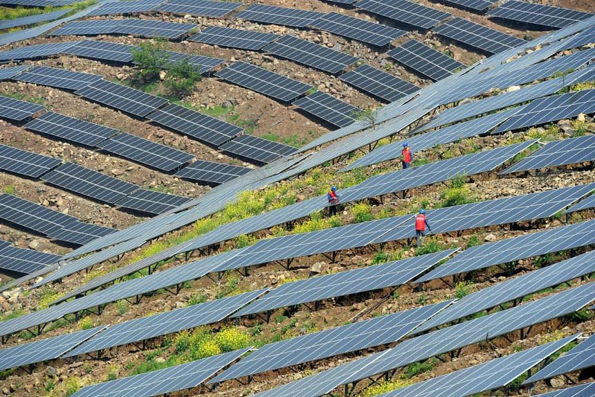 Chinese workers checking solar photovoltaic modules on a hillside in a village in Chuzhou, China, on April 13, 2017.