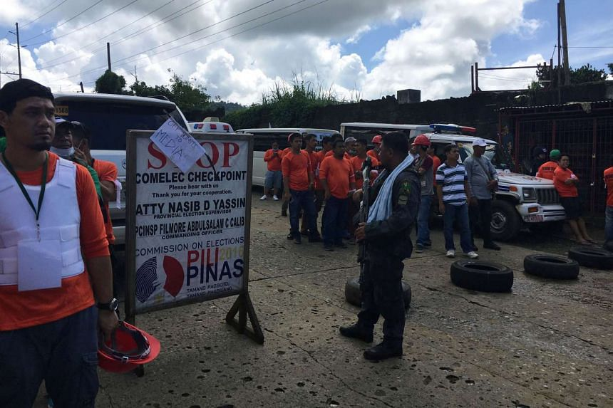 Rescue teams waiting at a police checkpoint after gun battles broke a ceasefire in Marawi, the Philippines, yesterday.