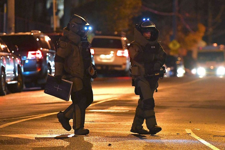 Australian police from the bomb squad unit walk near the site where a gunman was shot dead after holding a woman hostage in Melbourne.