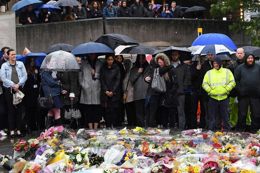 A woman reacts as people observe a minutes' silence on the south-side of the London Bridge in London on June 6, 2017, in memory of the victims of the June 3 terror attacks.