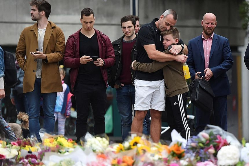 People gathering yesterday to mourn at a makeshift memorial on the south side of London Bridge near Borough Market, where flowers have been placed to remember the victims of the terror attack.