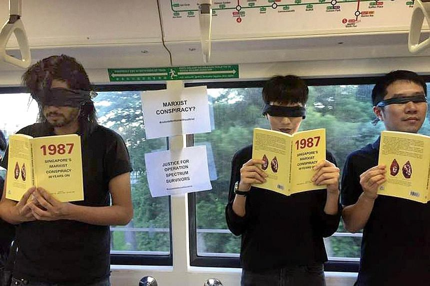 The group was seen riding a train on the North-South Line last Saturday while holding copies of a book launched by former ISA detainees last month and wearing blindfolds in a silent protest.