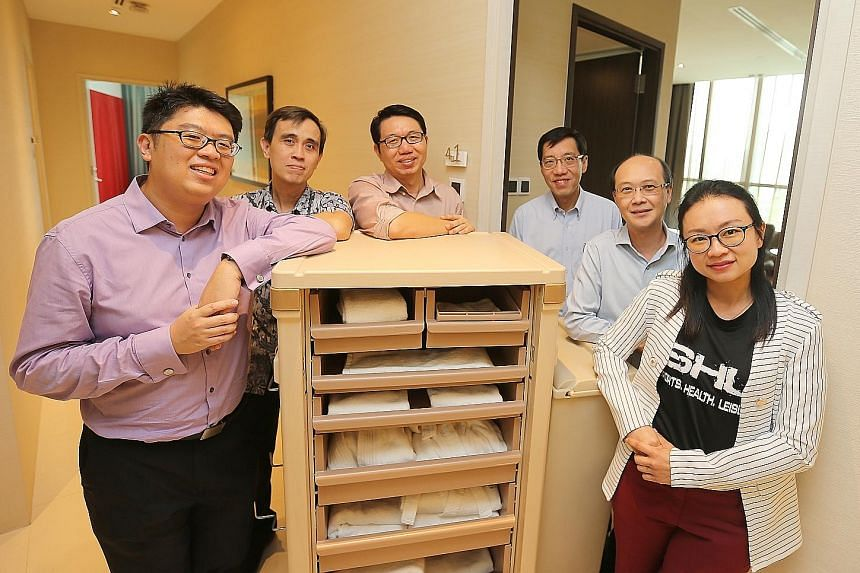 The team of Republic Polytechnic lecturers developing the motorised housekeeping cart includes Mr Michael Loke (from left), Dr Alex Ong, Mr Hong Ling Tim, Mr Tan Wee Siong, Mr Kelver Choo and Dr Jernice Tan. The cart in the picture is a regular non-m