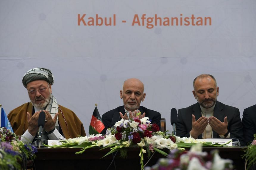 Afghan President Ashraf Ghani (centre) prays during an international peace conference at the Presidential Palace in Kabul on June 6, 2017.