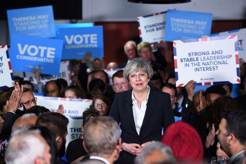British Prime Minister Theresa May reacts during a general election rally at the Odsal Stadium in Bradford, West Yorkshire, on June 5, 2017.
