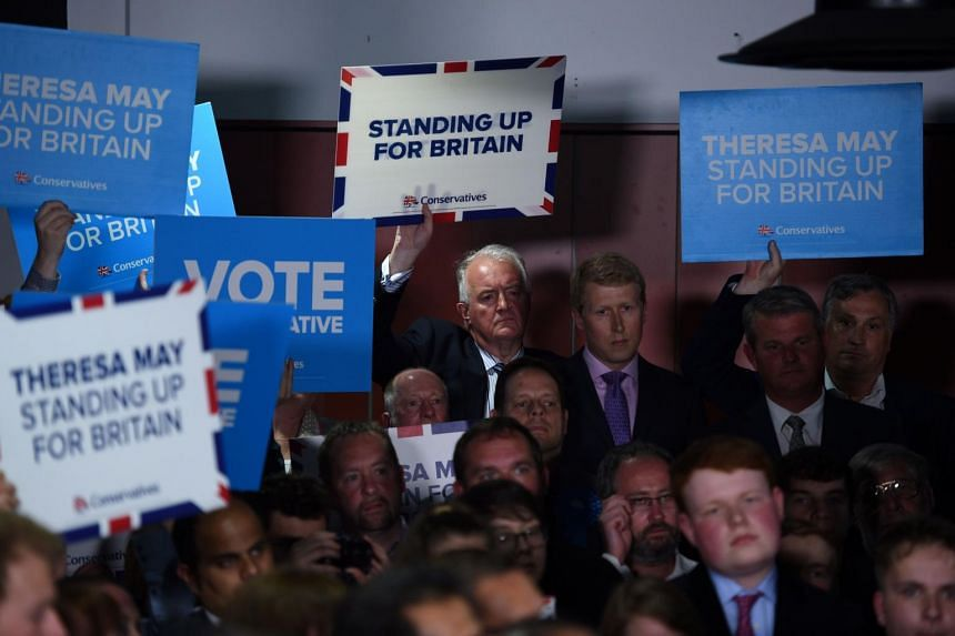Supporters of British Prime Minister Theresa May holds placards during a general election rally at the Odsal Stadium in Bradford, West Yorkshire, on June 5, 2017.