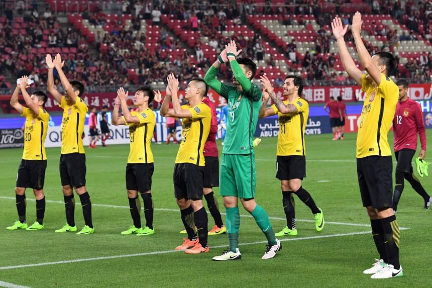 Guangzhou Evergrande's players applaud their fans after the victory during the AFC Champions League football match against Japan's Kashima Antlers in Kashima, Ibaraki prefecture on May 30, 2017.