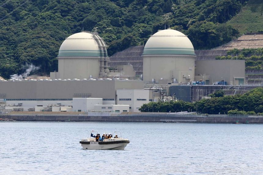 A boat of the Japan Coast Guard patrols in front of the No. 3 reactor (left) at the Takahama nuclear plant in Takahama, Fukui prefecture, some 350km west of Tokyo on June 6, 2017.
