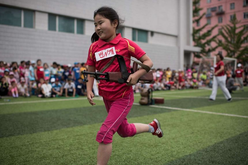A girl carrying a mock rifle completes an obstacle course as school children take part in sports games marking 'Children's Union Foundation day', in Pyongyang on June 6, 2017.