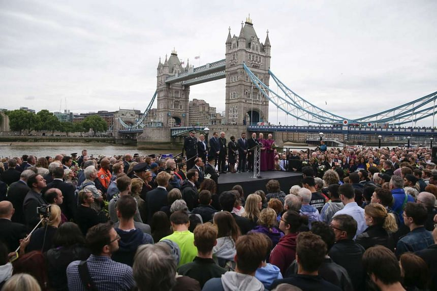 People gather for a vigil in Potters Fields Park in London on June 5, 2017 with Tower Bridge in the background to commemorate the victims of the terror attack.