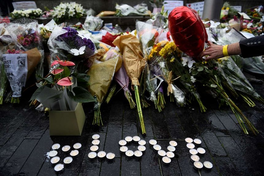 A person lays a floral tribute after a vigil at Potters Field Park, near the scene of the attack at London Bridge.
