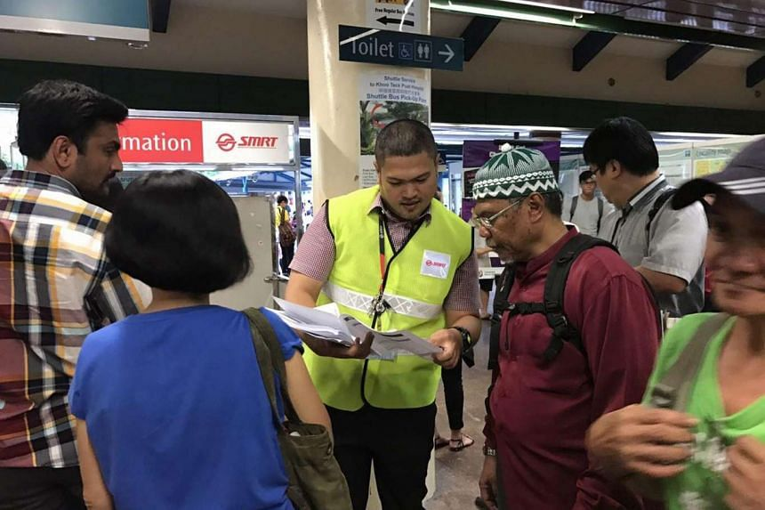 An SMRT employee handling out pamphlets on alternative modes of transport at Yishun station, after a delay on the North-South Line, on June 2, 2017.