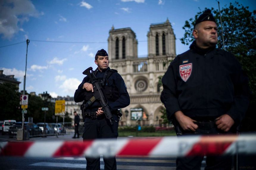 French police officers stand guard outside of the Notre Dame cathedral after a man attacked a police officer with a hammer, in Paris, France, on June 6, 2017.