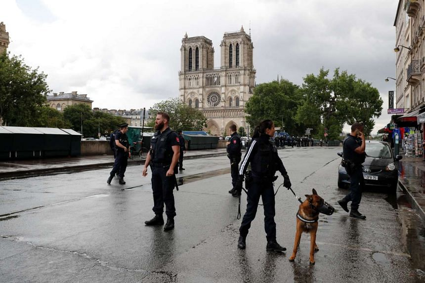 French police stand at the scene of the shooting incident near Notre Dame Cathedral.