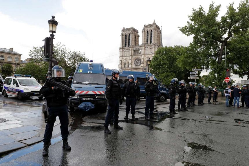 French police stand at the scene of thea shooting incident near Notre Dame Cathedral.