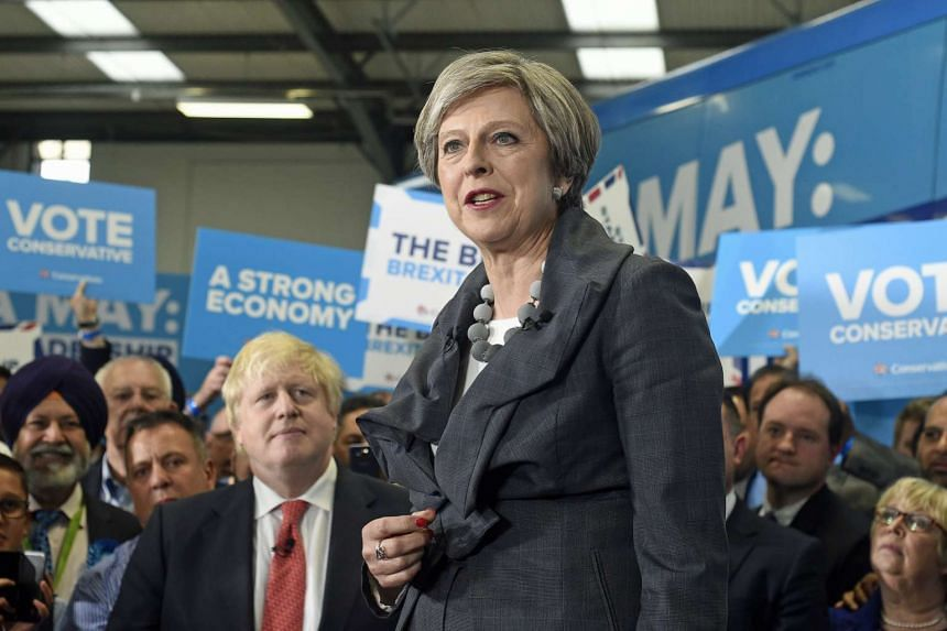 Mrs Theresa May delivering a speech watched by British Foreign Secretary Boris Johnson (left) on Tuesday (June 6).
