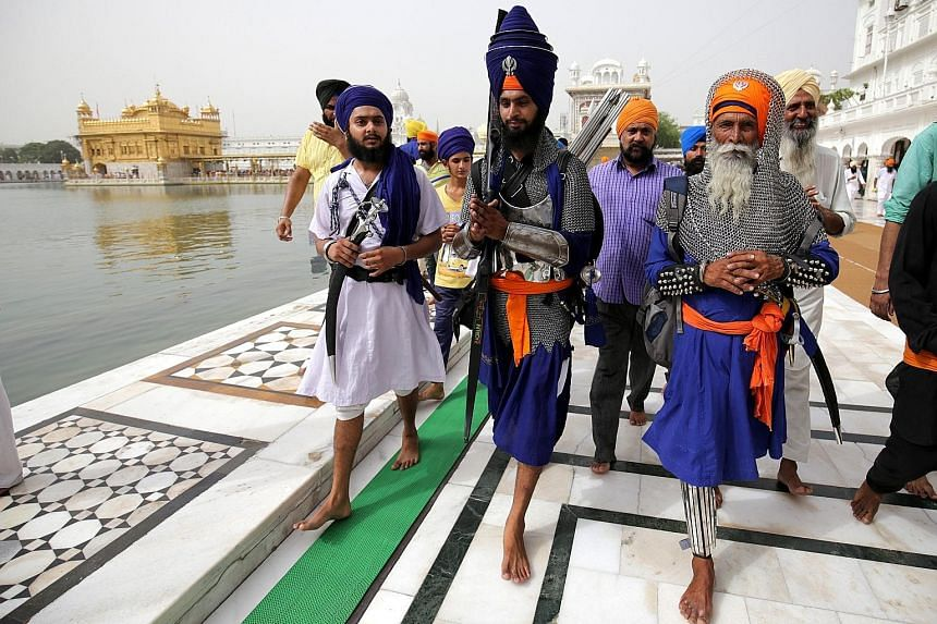 Sikh men in warrior attire preparing to pay their respects at the Golden Temple, the holiest of Sikh shrines, on the 33rd anniversary of Operation Blue Star in Amritsar, India, yesterday. The operation took place from June 3 to 8 in 1984, when the In