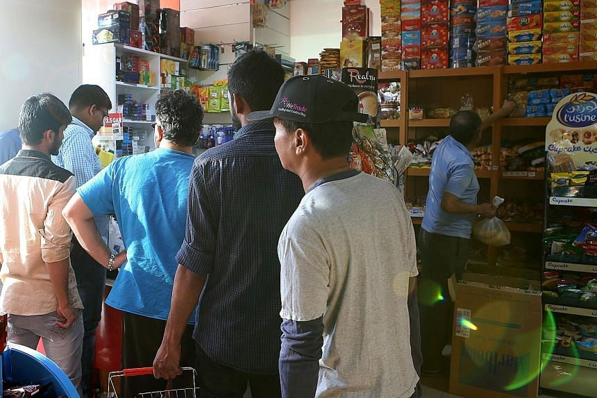 People buying food at a shop in Doha on Monday, before panic-buying set in after five Arab nations cut ties with Qatar.