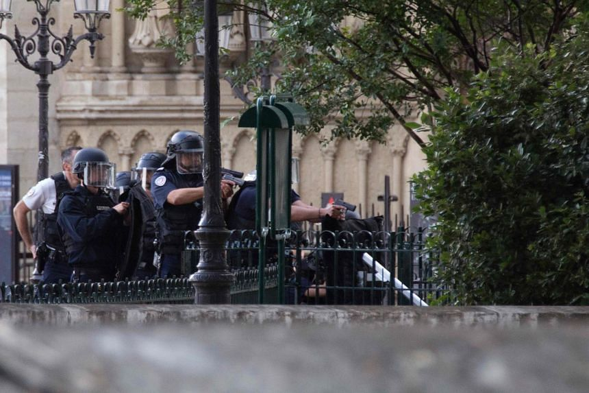French policemen point their weapons near the site of an attack at the entrance of Notre-Dame cathedral in Paris on June 6, 2017.