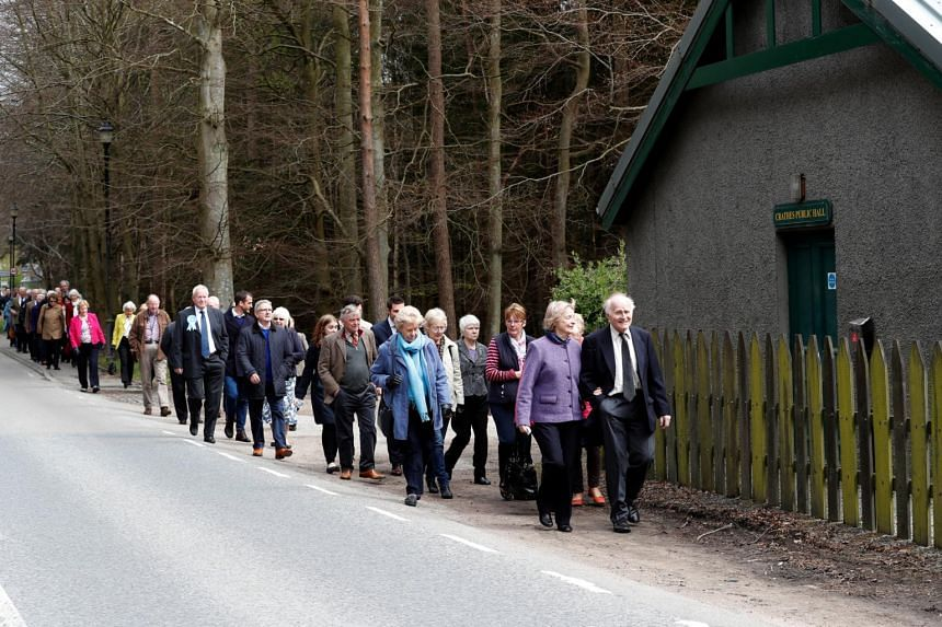 People arrive to hear Britain's Prime Minister Theresa May speak at an election campaign rally near Aberdeen in Scotland.