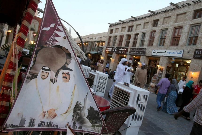 People walking past a banner bearing portraits of former emir of Qatar Sheikh Hamad bin Khalifa al-Thani (right) and his son current leader Sheikh Tamim bin Hamad al-Thani displayed at Souq Waqif in Doha.