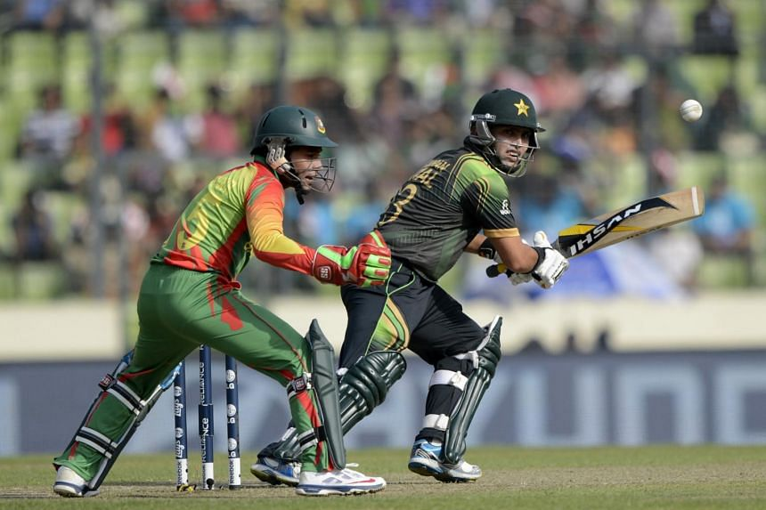 Pakistan cricketer Kamran Akmal (right) playing a shot as Bangladesh captain Mushfiqur Rahim looks on during the ICC World Twenty20 tournament Group 2 cricket match.