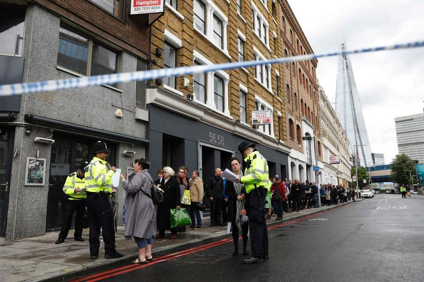 Police officers check the names of people, previously allowed into buildings within the police cordon on Borough High Street, in London, on June 6, 2017