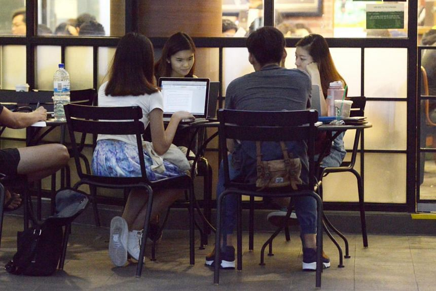 A group of teenagers using their laptops.